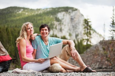Relaxed couple with laptop while camping