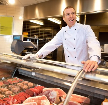 View of frozen meat with cheerful chef
