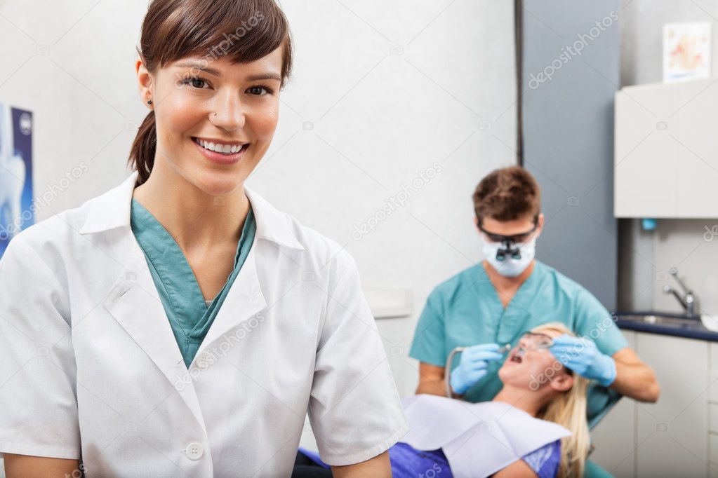 Assistant with dentistry work in the background