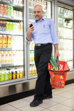 Man with Grocery Basket and Mobile Phone