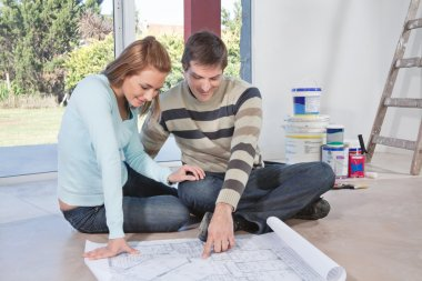 Man showing blueprint of their new house to his wife