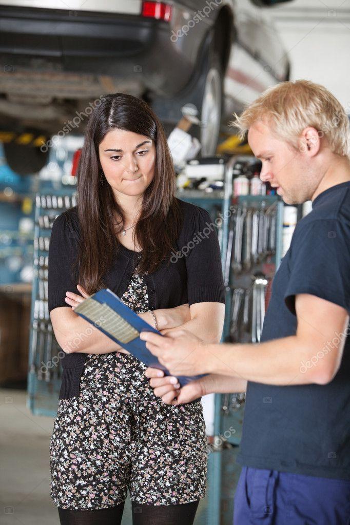 Mechanic showing bill to a woman