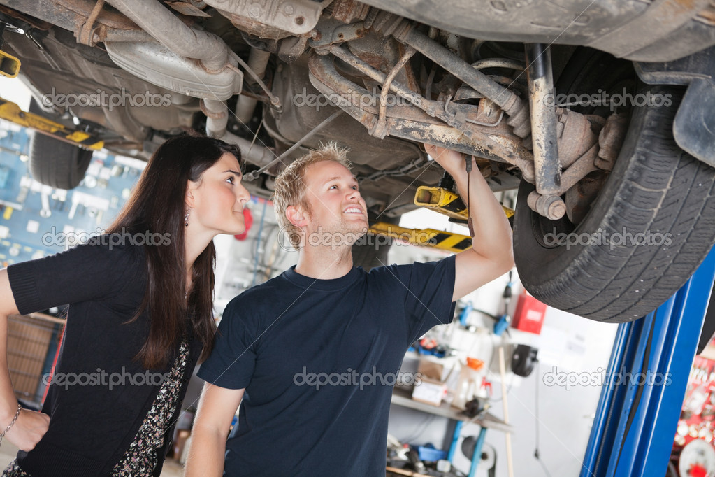 Woman and mechanic looking at car repairs