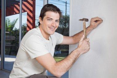 Man hammering the wall