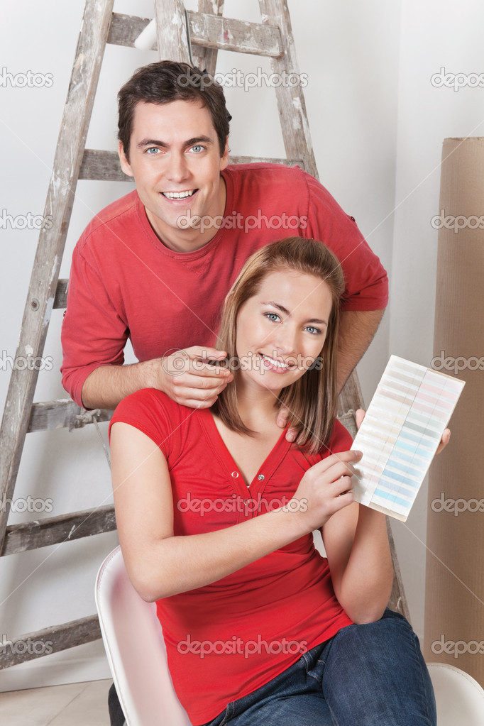 Young happy couple pointing at color card