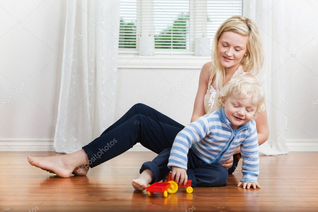 Smiling young mother sitting with child playing on floor