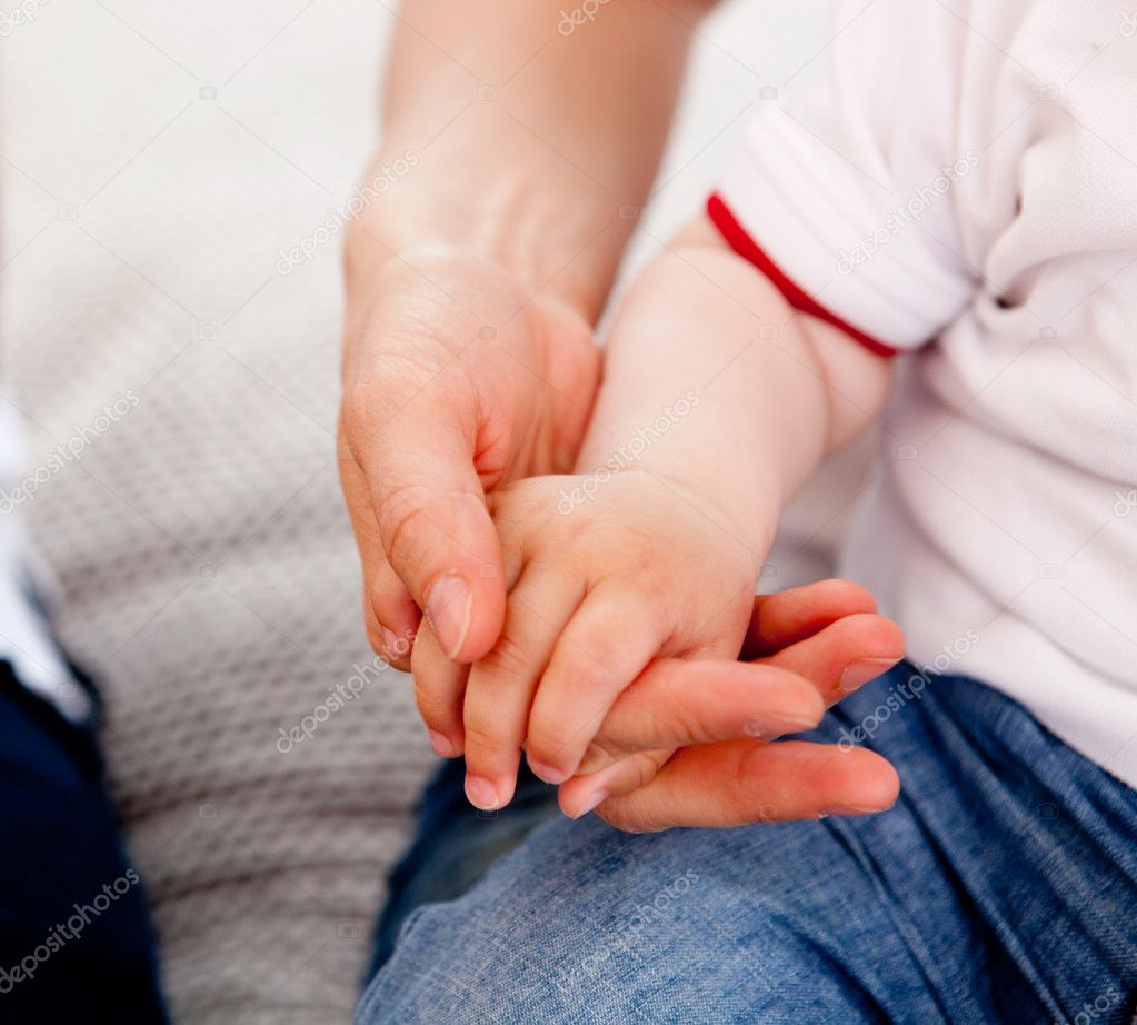 Detail of a small toddler boy holding his mothers hand