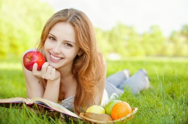 A beautiful young girl with an apple lying on the grass and reading a book beside a basket of fruit is, on a background of green nature stock vector