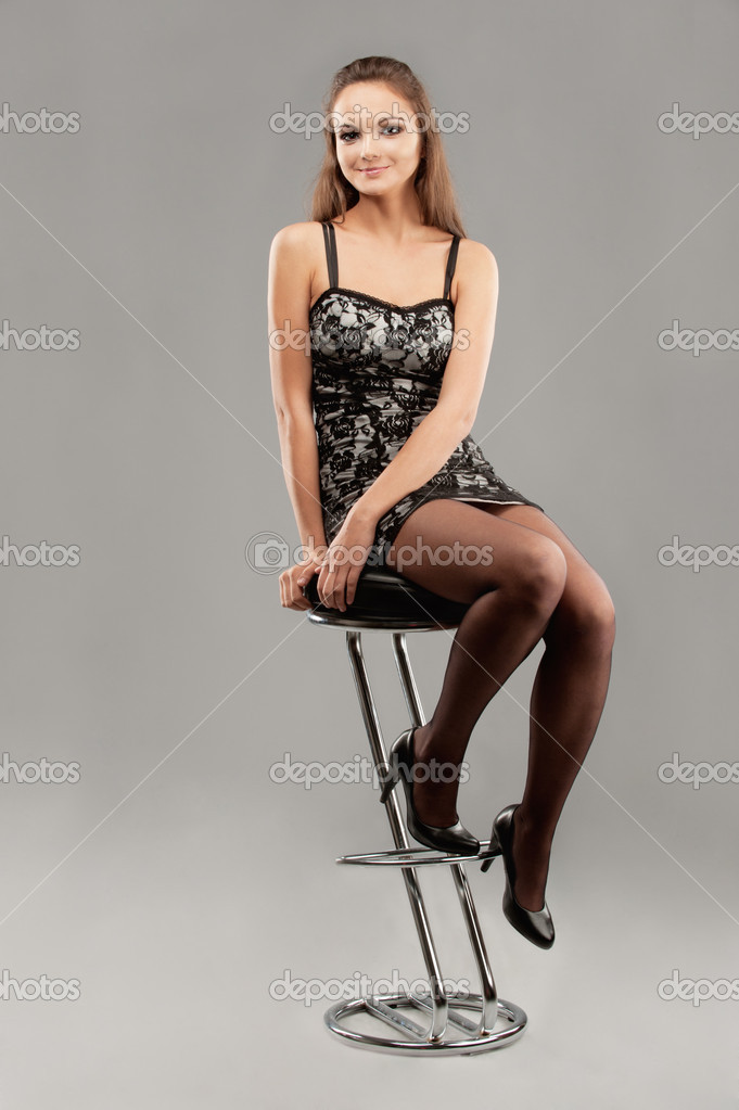 Young Woman Sits On Bar Chair Stock Photo