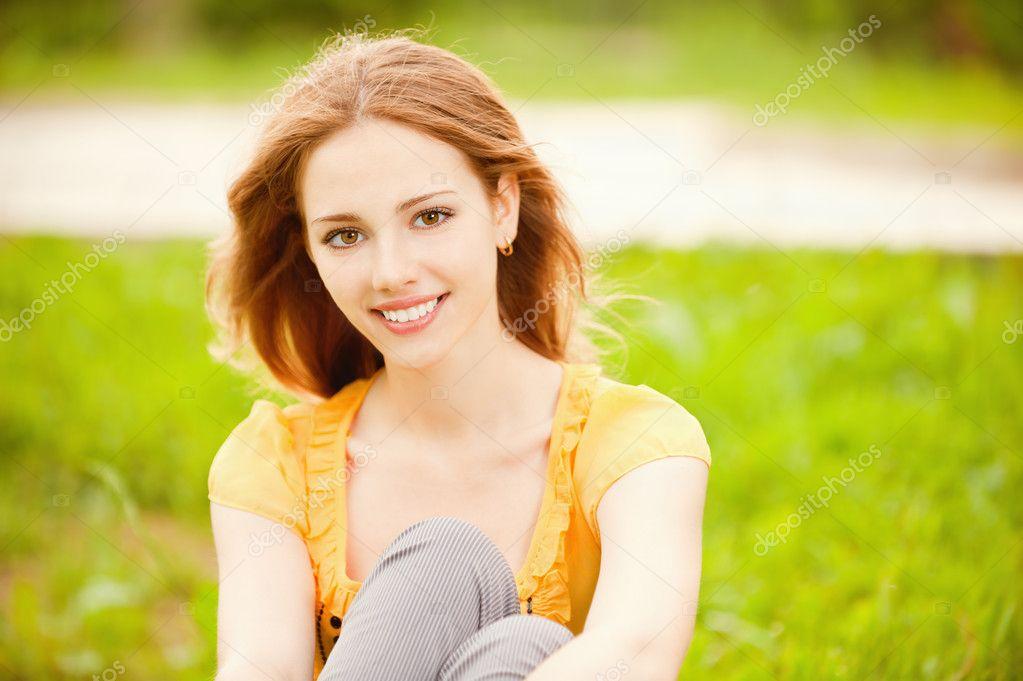 Beautiful girl sits on lawn