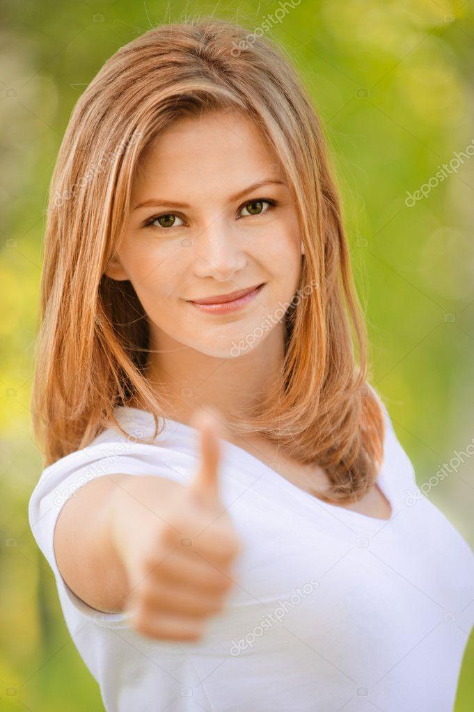 Smiling woman lifts thumb
