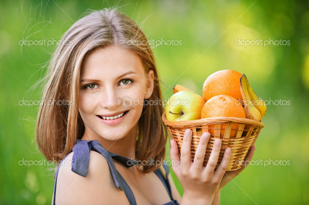 Woman holds basket with fruit
