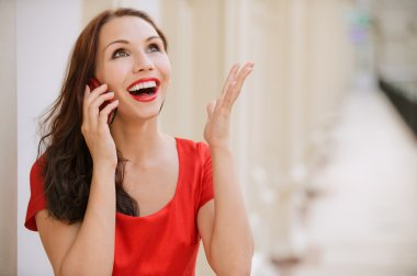 Young woman talks by mobile phone