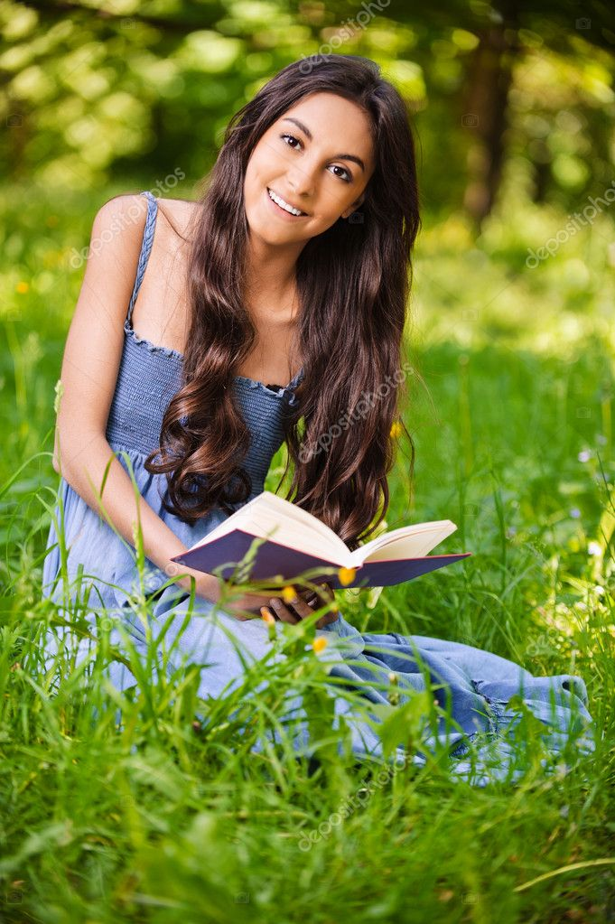 Portrait of beautiful young long-haired woman with book