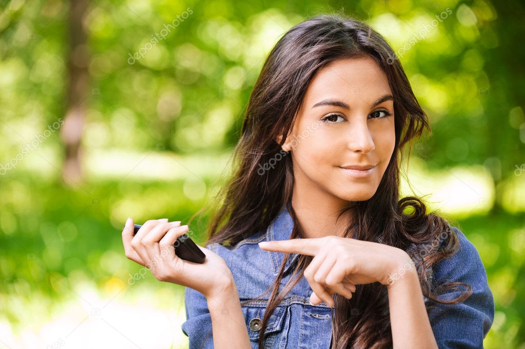 Portrait of beautiful young long-haired woman with mobile phone