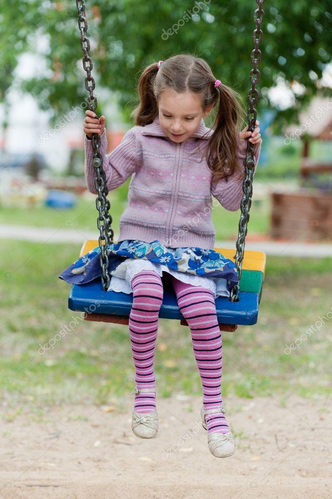 petite fille souriante joyeuse en vtements violettes en jouant sur la balanoire image de bestphotostudio