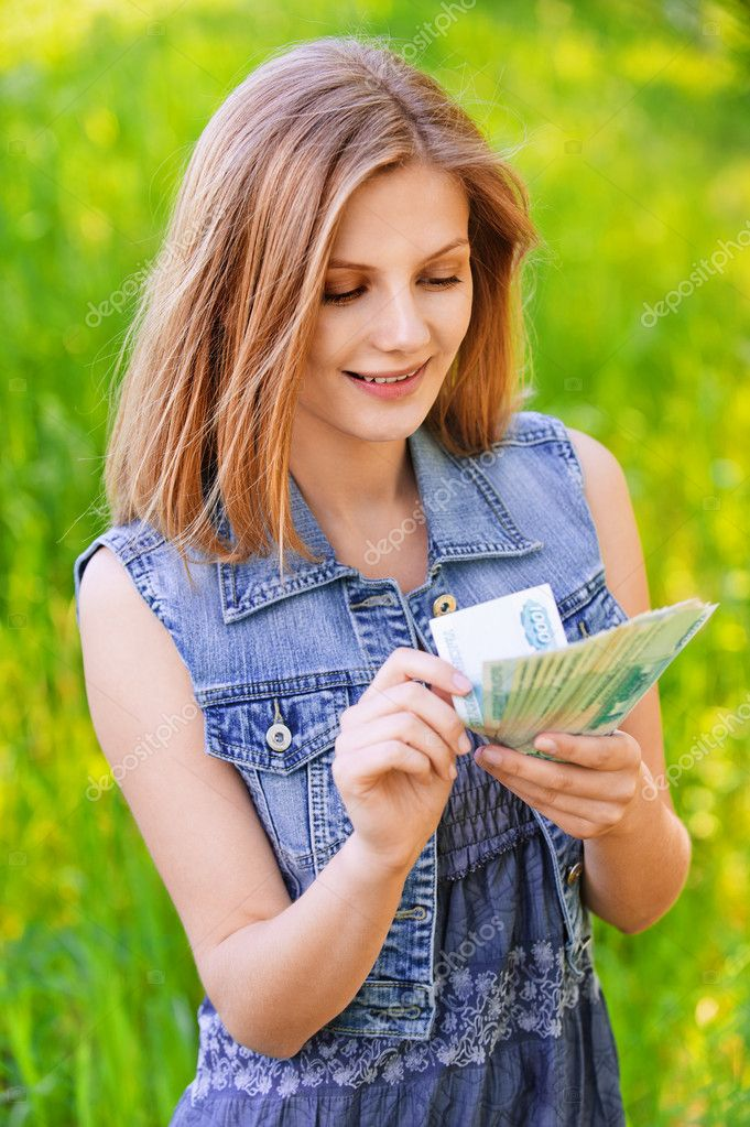 Portrait of young woman counting money