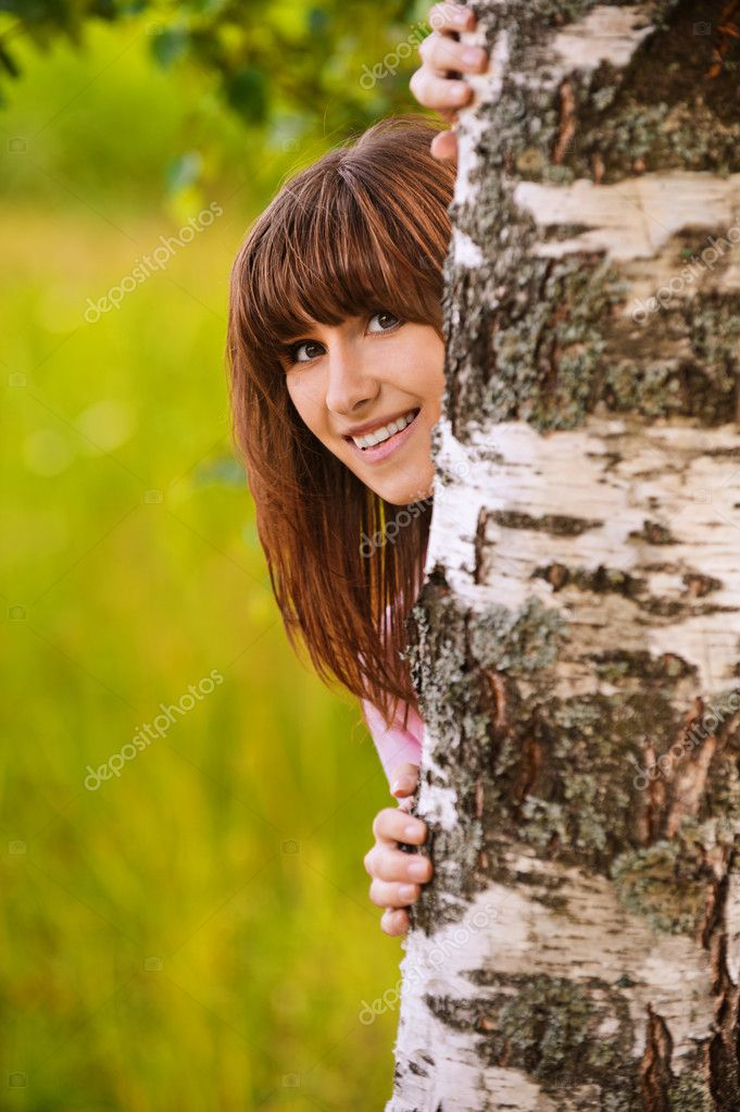 Portrait of laughing girl looking from behind tree