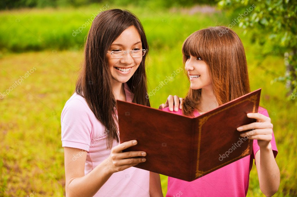 Two women read a book