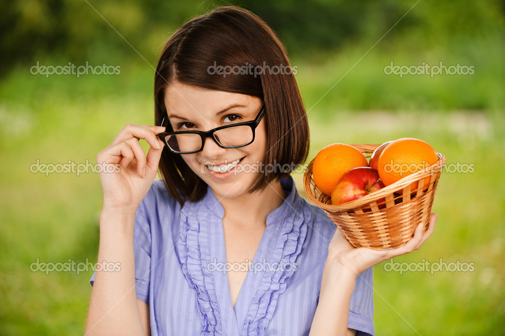 Young joyful woman wearing glasses holding basket with fruits