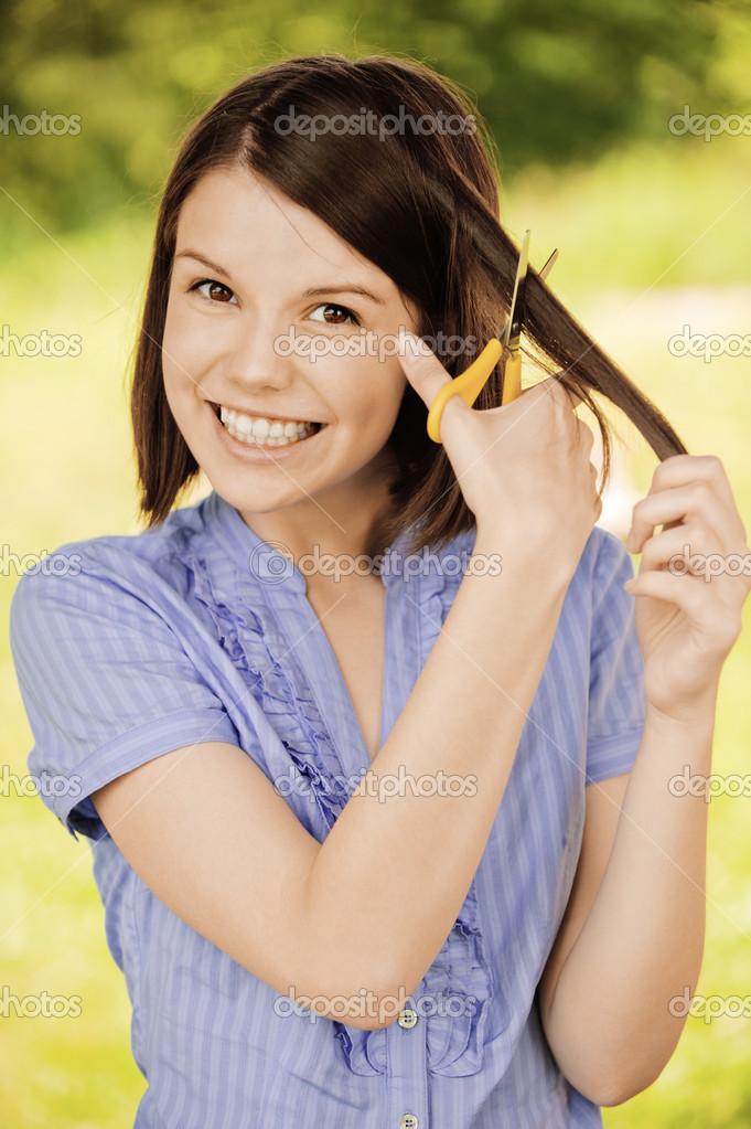 Portrait of brunette woman cutting her hair
