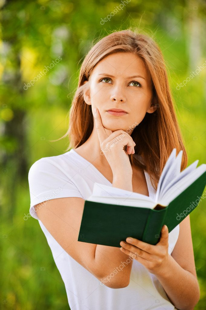 Young thoughtful woman holding book