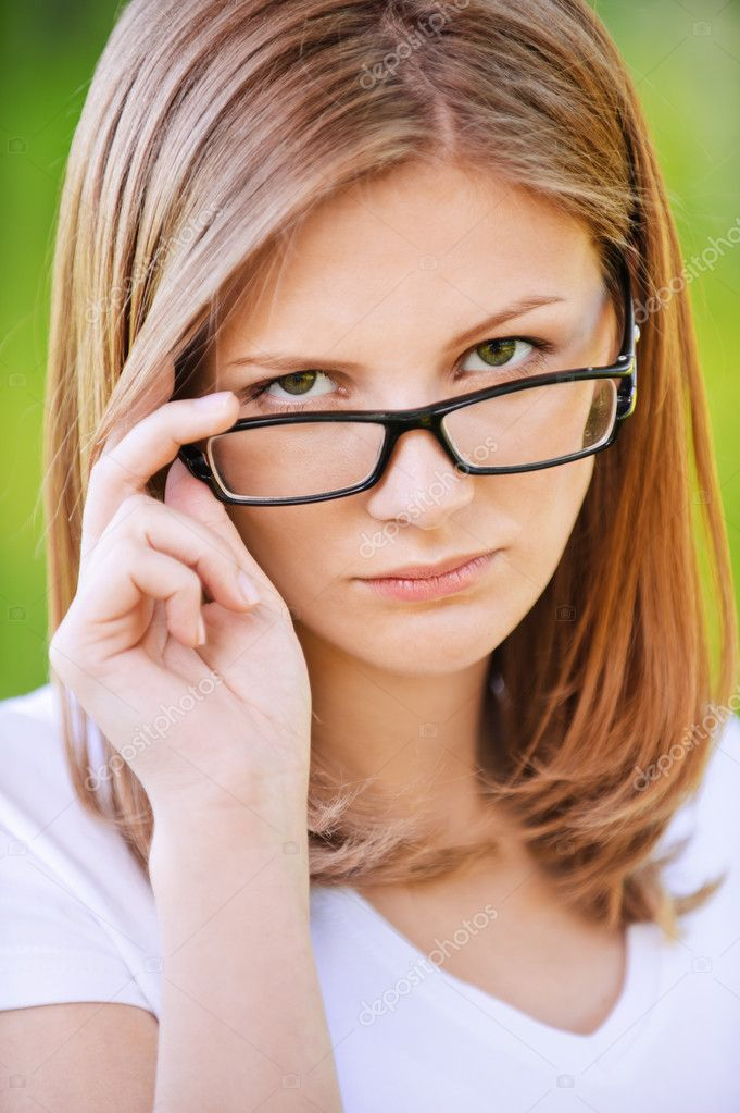 Portrait of strict woman looking above her glasses