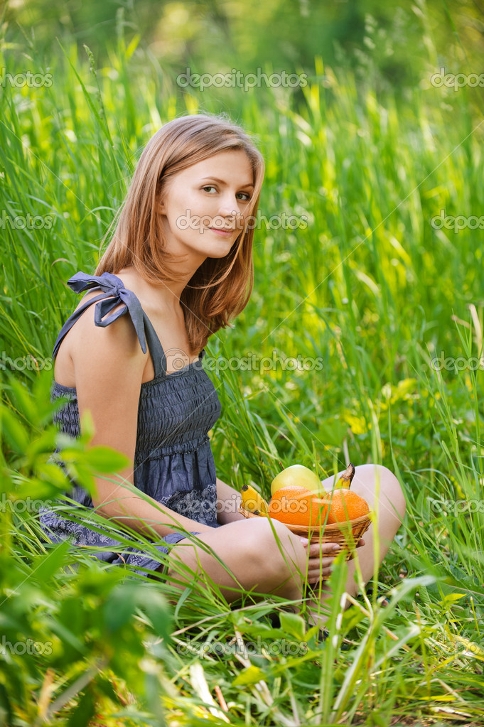 Portrait of young woman sitting in grass with basket full with f