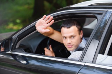 Portrait of young man driving car and greeting somebody with han