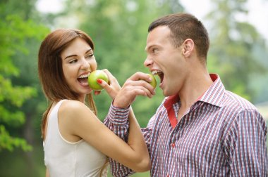 Two young happy eating apples