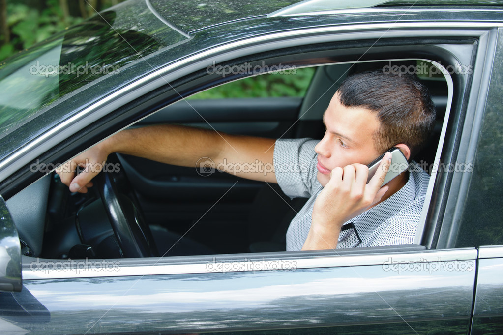 Young man speaking on telephone and driving car