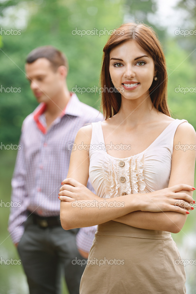 e49bdbc897 Two   young smiling dark-haired woman wearing beige dress and young  handsome man standing at summer green park. — Photo by BestPhotoStudio