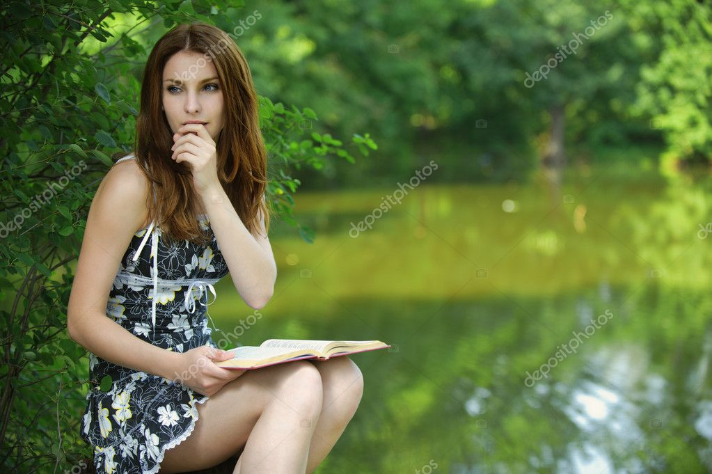 Portrait of young woman holding book