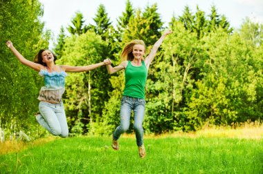 Two young women jumping