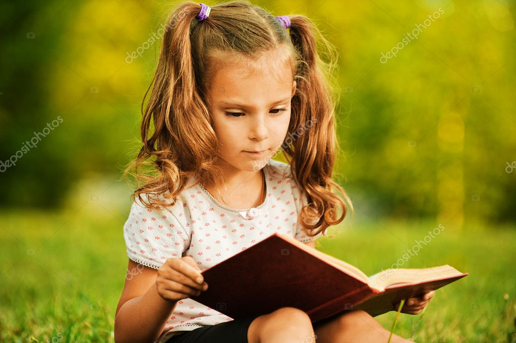 Portrait of little cute girl reading book