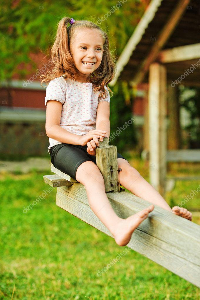 Little smiling girl on seesaw