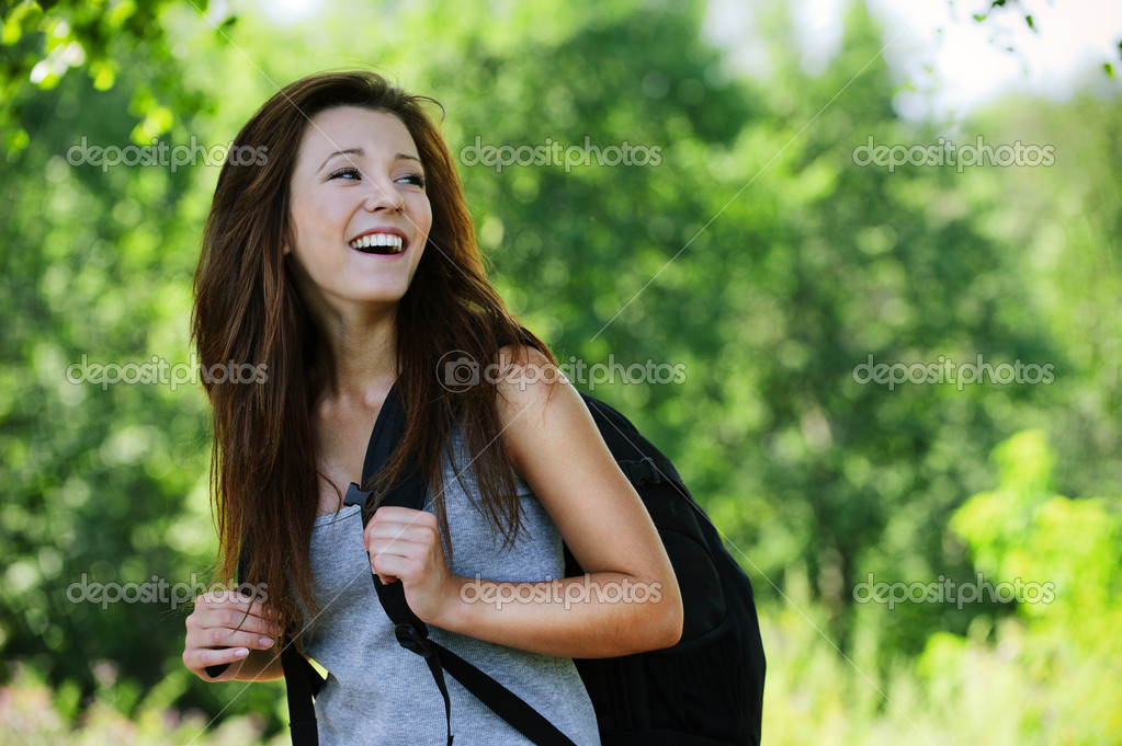 Pretty laughing girl wearing backpack