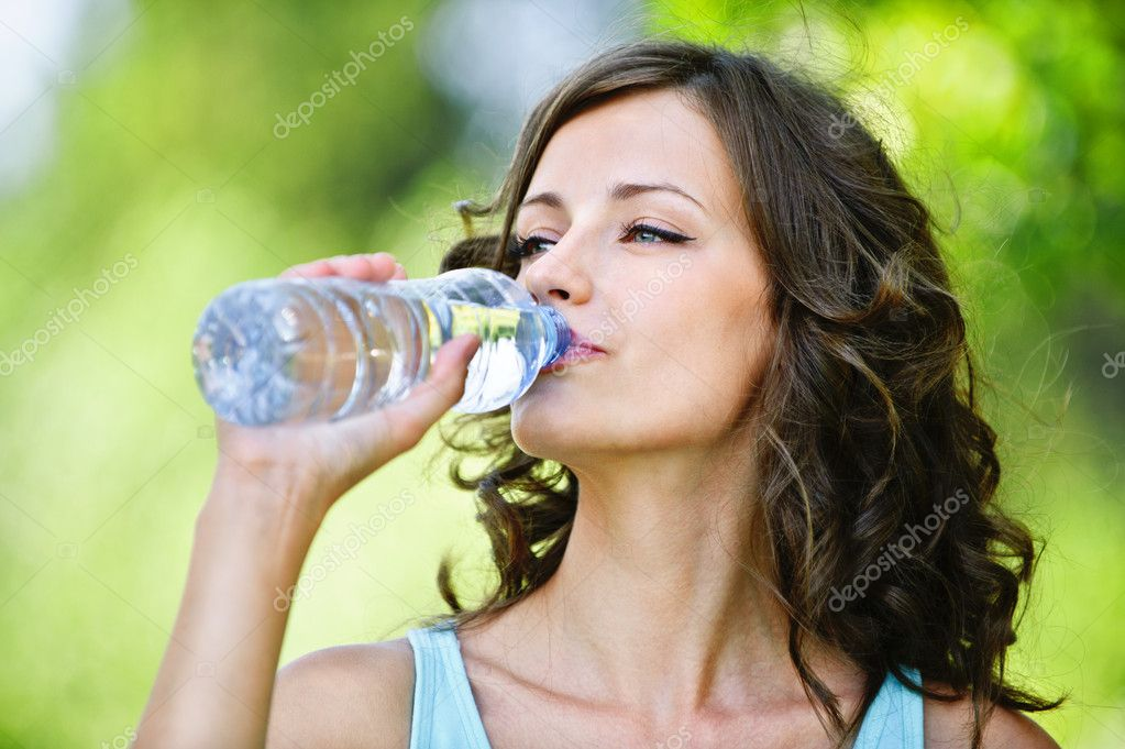 Young dark-haired woman drinking water
