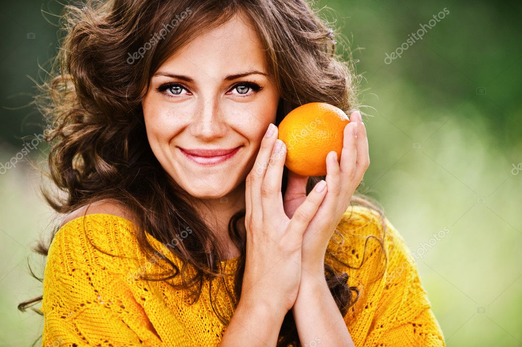Pretty woman holding orange