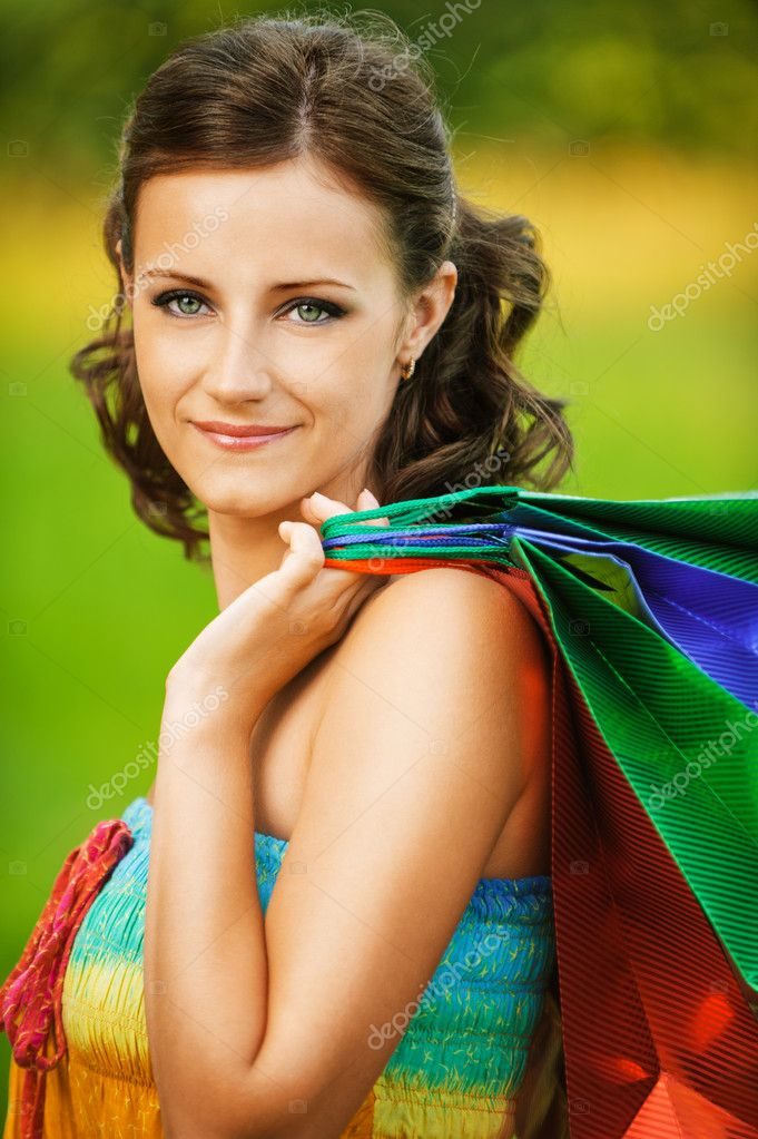 Portrait of young smiling woman holding many bags