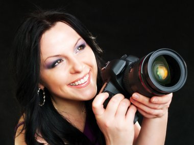 Photographer woman holding camera over dark background