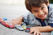 Fotografie Kind spielt mit Autos Spielzeug