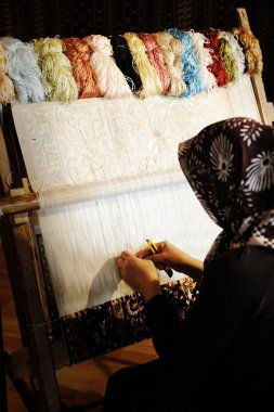 Woman working at the loom. Oriental Muslim national crafts. Focus on the fa