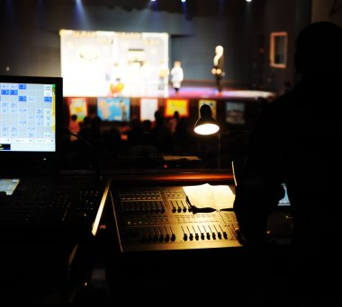Sound engineer at mixing desk, children performance out of focus
