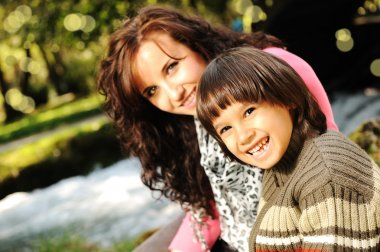 Mom and kid in nature beside the river