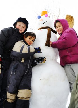 Children playing happily in snow making snowman, winter season