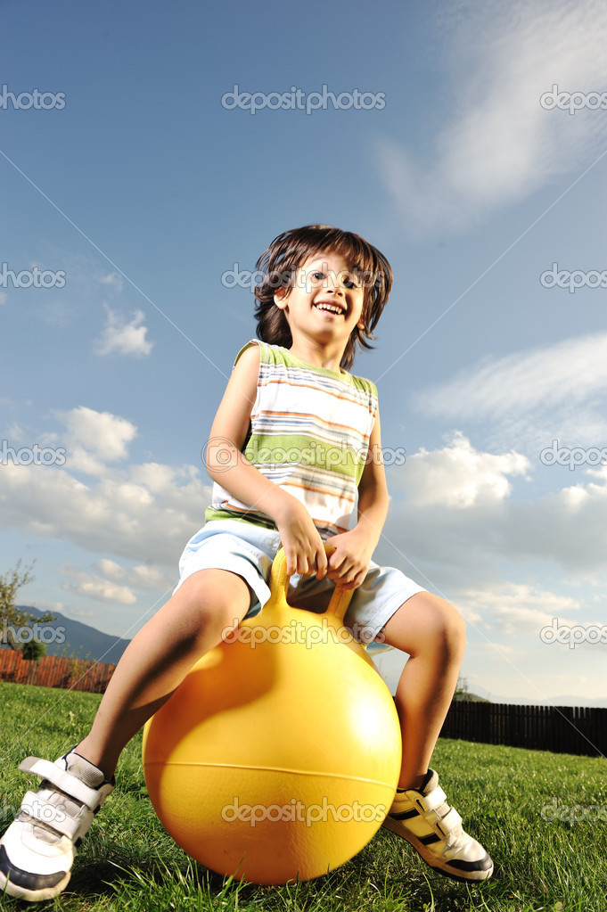 Little happy boy playing with big ball and jumping with slight motion up, s