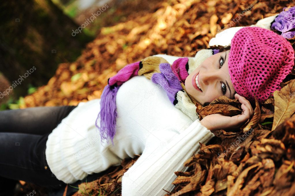 Young beauty girl laying on autumn ground and leaves, perfect face and natu