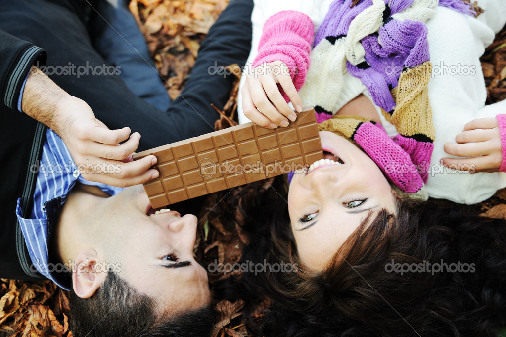 Young beauty girl and her boyfriend eating together chocolate in nature tog