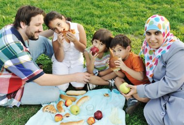 Muslim family, mother and father with three children together in nature sit